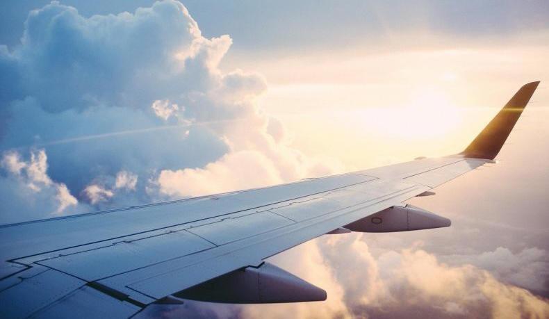 Repülőgép szárnya felhők és nap között